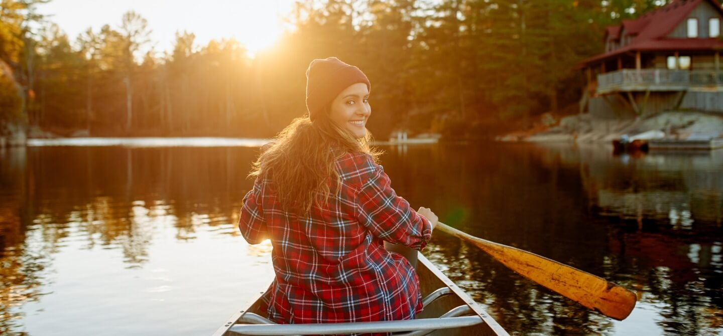 girl paddling canoe in Canadian lake