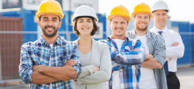 Group of construction worker builders in hardhats outdoors